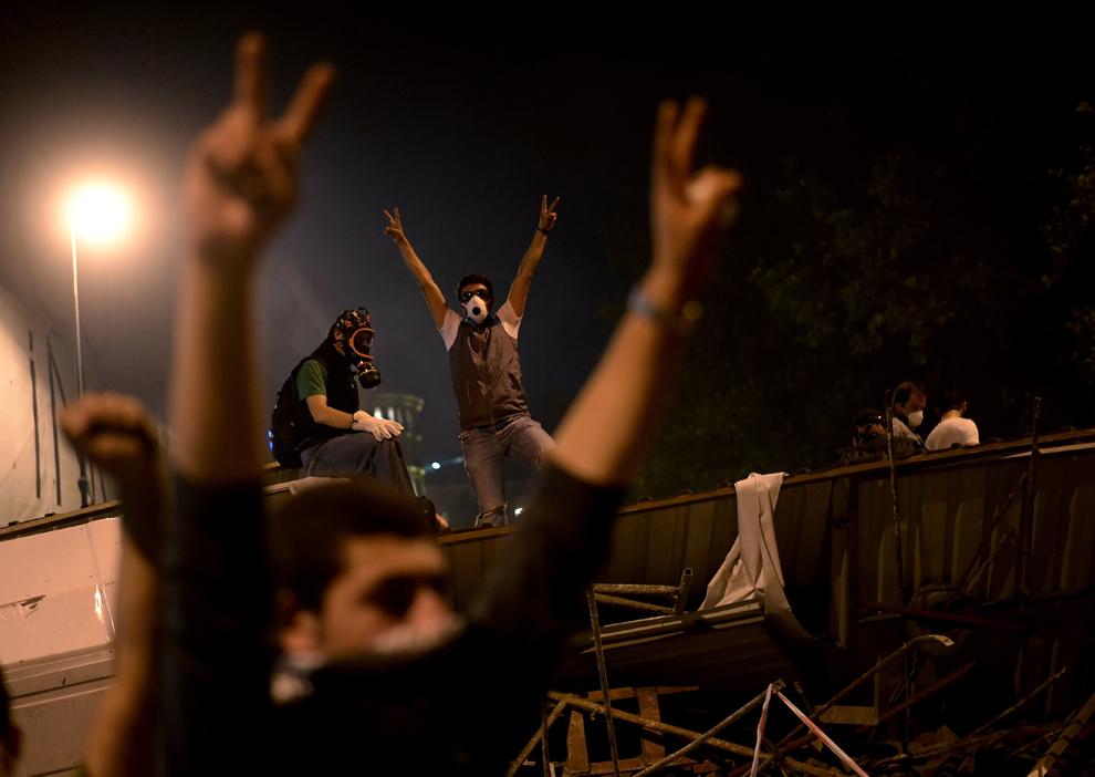 Mai mulţi protestatari arată semnul victoriei în timpul unei demonstraţii împotriva distrugerii parcului Taksim, în Istanbul, Turcia, marţi, 4 iunie 2013.