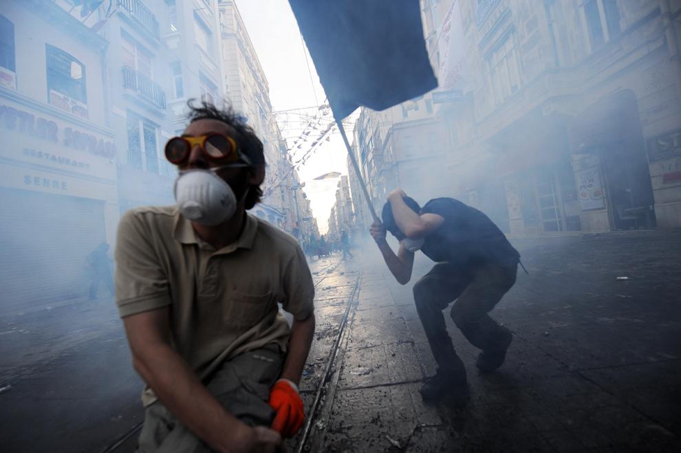 Doi bărbaţi sunt înconjuraţi de gaze lacrimogene în timpul unor lupte de stradă cu forţele de ordine, în Piaţa Taksim, Istanbul, Turcia, vineri, 31 mai 2013.