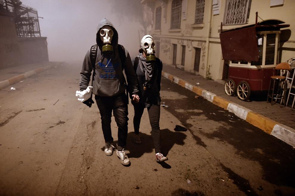 Un cuplu ce poartă măşti de gaze se plimbă pe o stradă, în Istanbul, Turcia,  marţi, 4 iunie 2013.