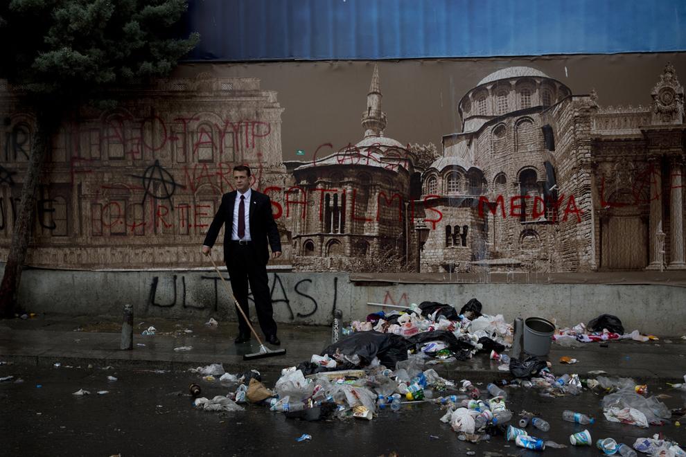 Un manager de hotel mătura gunoiul lăsat de protestatari, în Piaţa Taksim din Istanbul, Turcia, duminică, 2 iunie 2013.