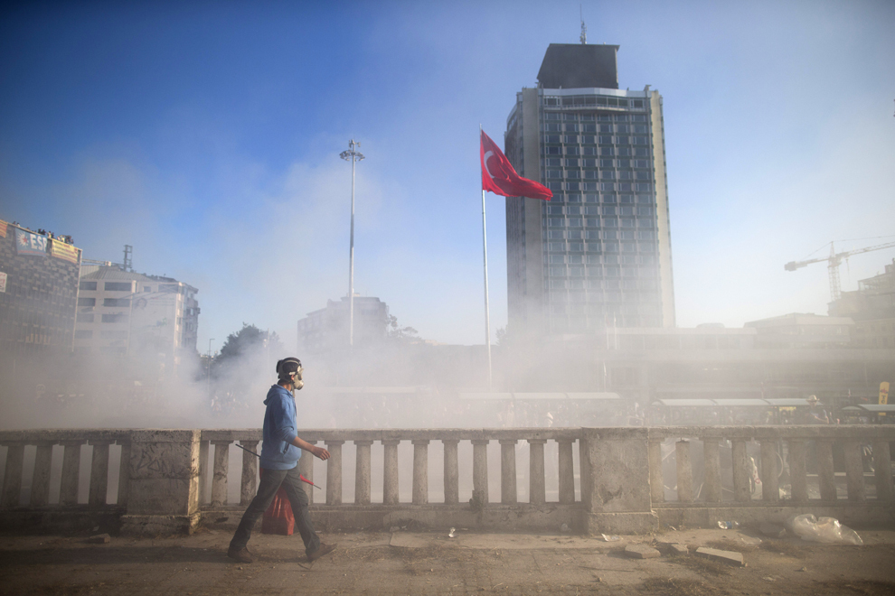 Un bărbat este înconjurat de gaze lacrimogene în timpul unui protest, în Piaţa Taksim din Istanbul, Turcia, luni, 3 iunie 2013.