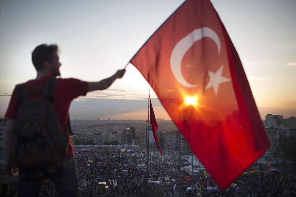 Un protestatar flutură un steag pe acoperişul unei clădiri din Piaţa Taksim, în Istanbul, Turcia, marţi, 3 iunie 2013.