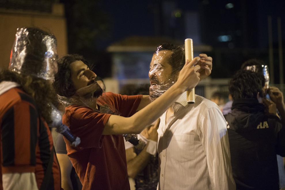 Participanţii la un protest îşi acoperă feţele cu folii de plastic, în timpul unor lupte de stradă cu forţele de ordine, în Istanbul, Turcia, marţi, 4 iunie 2013.