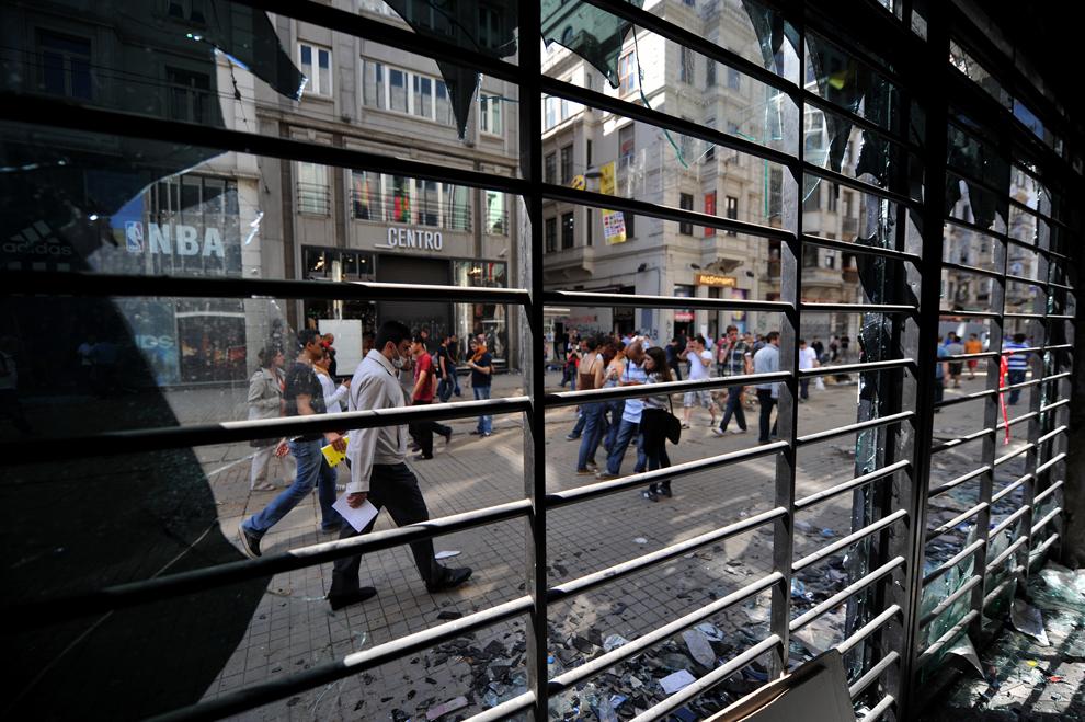 Protestatari pot fi văzuţi prin vitrina spartă a unui magazin din Piaţa Taksim din Istanbul, Turcia, sâmbătă, 1 iunie 2013.