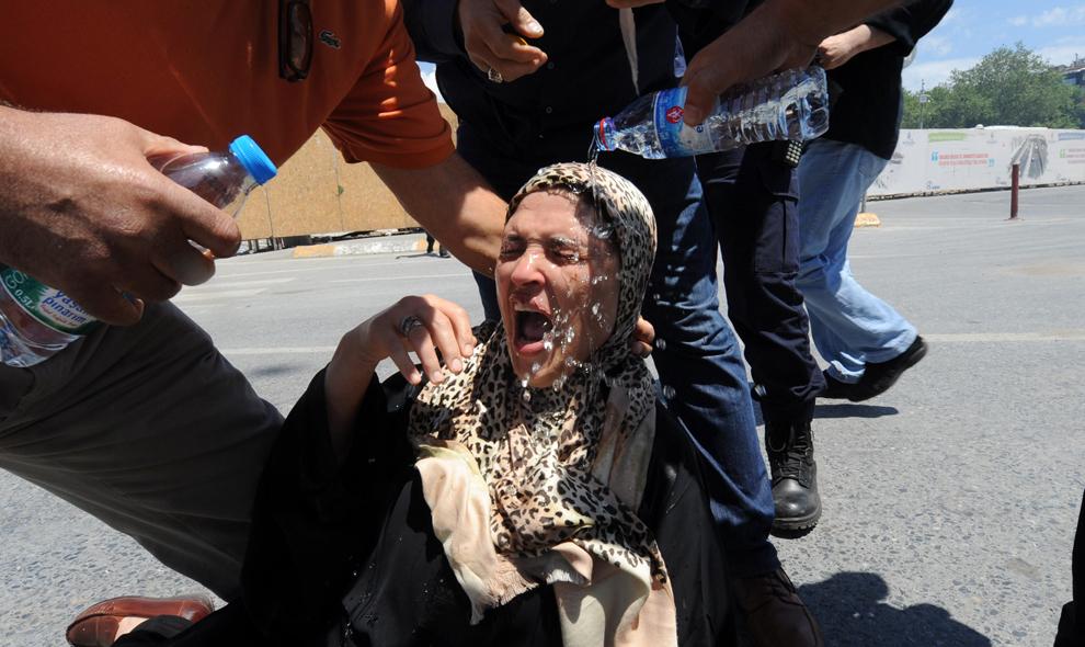 Protestatari toarnă apă pe faţa unei femei după ce aceasta a cazut, în timpul luptelor stradale cu forţele de ordine, în Piaţa Taksim din Istanbul, Turcia, sâmbătă, 1 iunie 2013.
