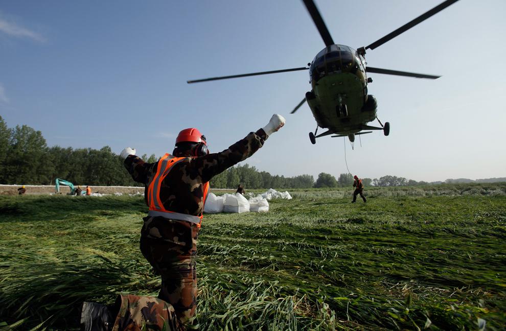 În timp ce un un elicopter militar ajută serviciile de intervenţie, soldaţi maghiari consolidează un baraj pe unul dintre malurile inundate, în satul Gyorujfalu, vineri, 7 iunie, 2013.