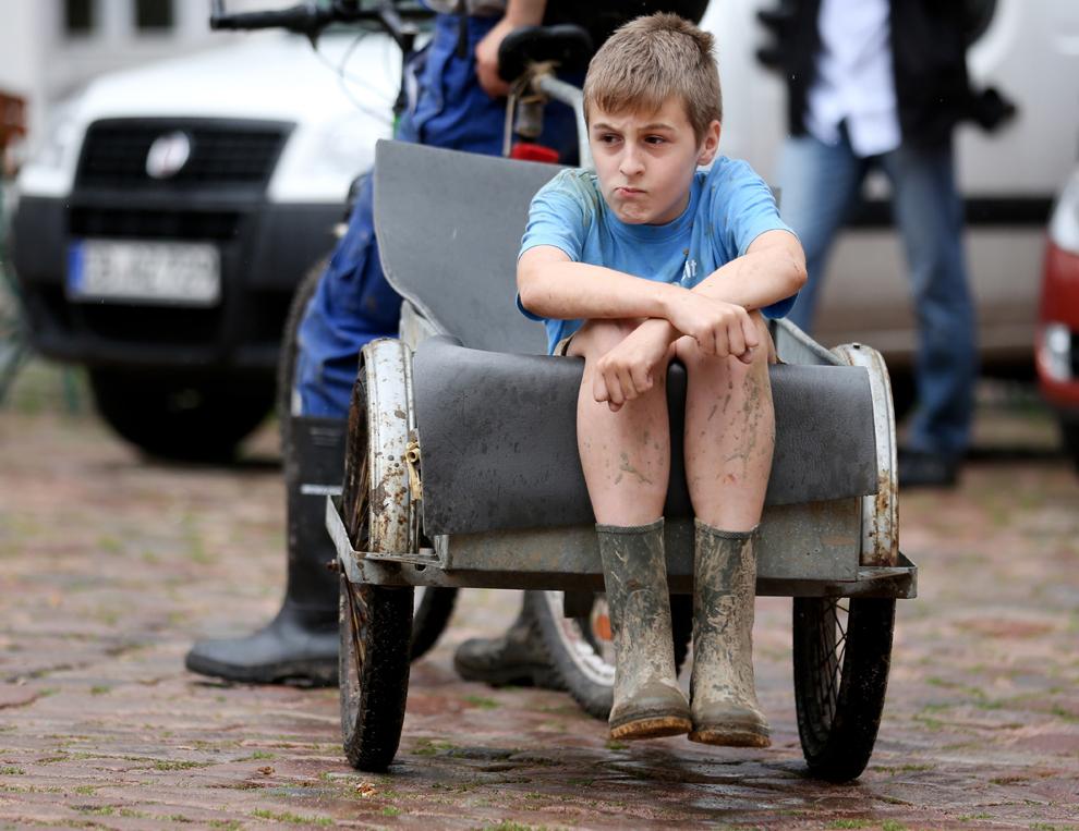 Un copil purtând cizme de cauciuc stă în ataşul unei biciclete, în orasul Meissen, lovit de inundaţii, în estul Germaniei, duminică, 9 iunie, 2013.