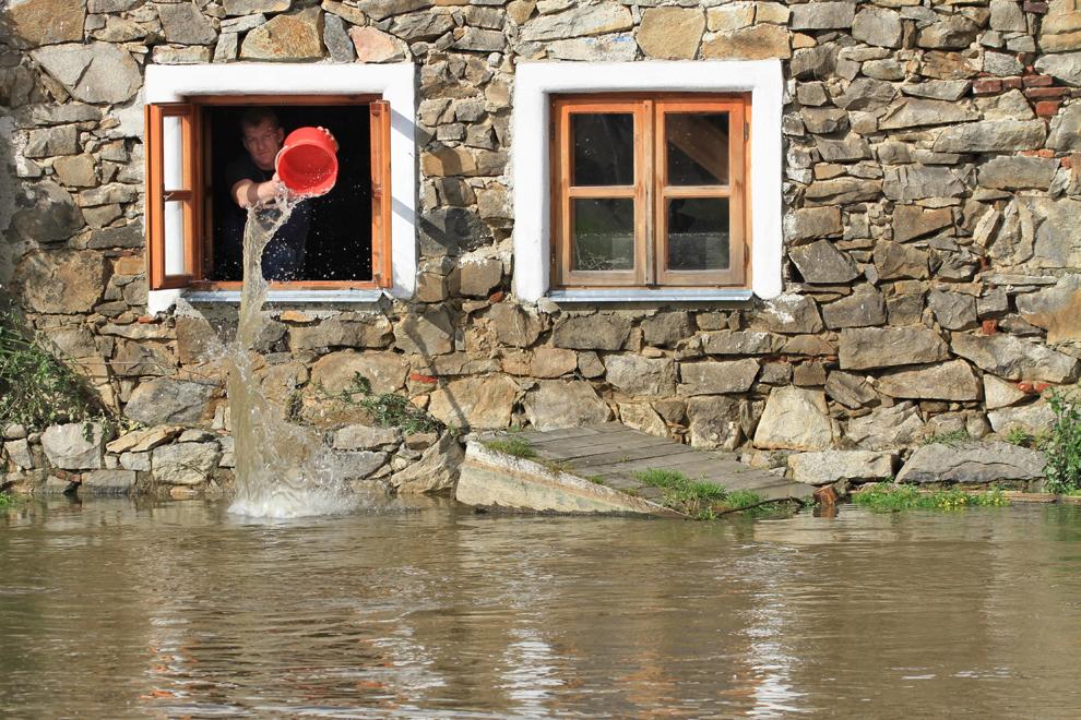Un bărbat scoate apă pe geamul unei case, lângă Pisek, Cehia, miercuri, 5 iunie, 2013.