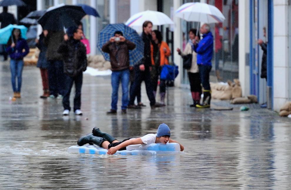 Un tânăr vâsleşte de pe o saltea gonflabilă, pe străzile inundate ale centrului istoric al oraşului Passau, Germania, luni, 3 iunie, 2013.