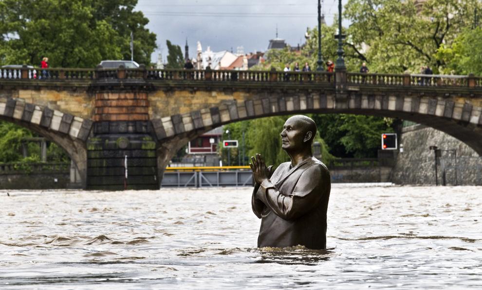 O statuie a liderului spiritual Sri Chinmoy realizată de sculptorul britanic Kaivalya Torphy este parţial scufundată sub apele râului Vltava, în centrul Pragăi, Cehia, duminică, 2 iunie 2013.