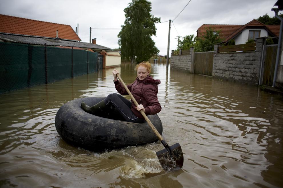 O localnică traversează o stradă inundată de raul Elba folosindu-se de un pneu şi o lopată, în Melnik, Cehia, marţi, 4 iunie 2013.