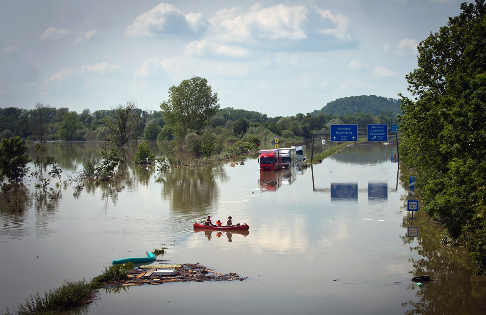 O familie trece într-o canoe pe lângă vehicule inundate pe autostrada A3, după ce fluviul Dunărea a ieşit din matcă, vineri, 7 iunie, 2013.