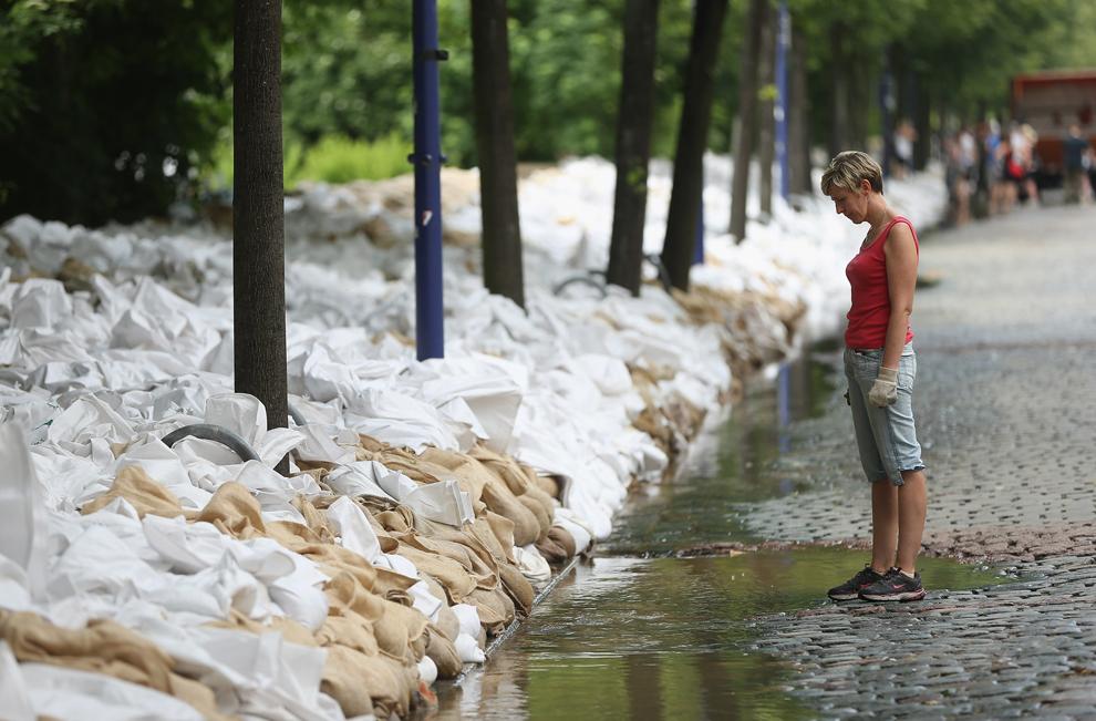 O femeie priveşte apa în timp ce saci umpluţi cu nisip, pregătiti de voluntari, pot fi vazuti pe marginea unei strazi din Magdeburg, Germania, duminică, 9 iunie, 2013.