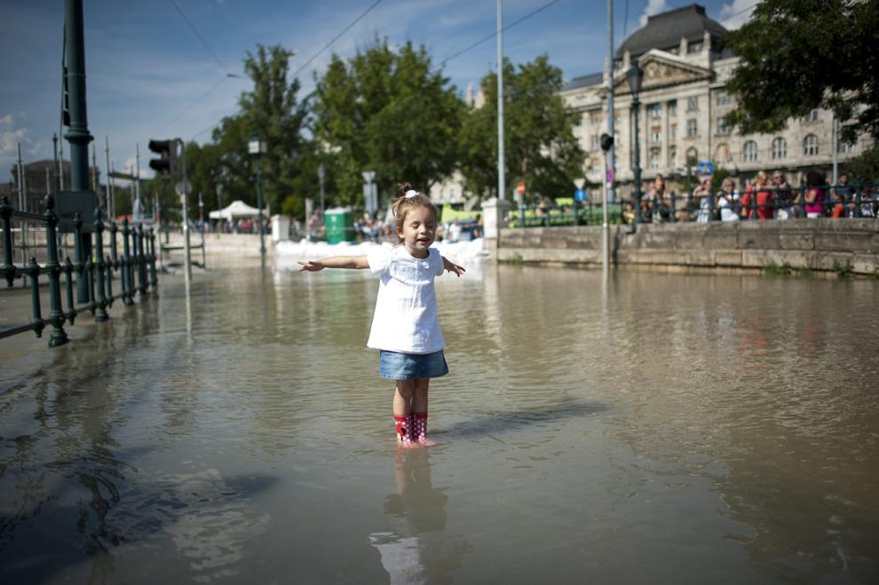 O fetiţă se joacă în apa Dunării care a inundat mai multe zone din Budapesta, duminică, 9 iunie 2013.