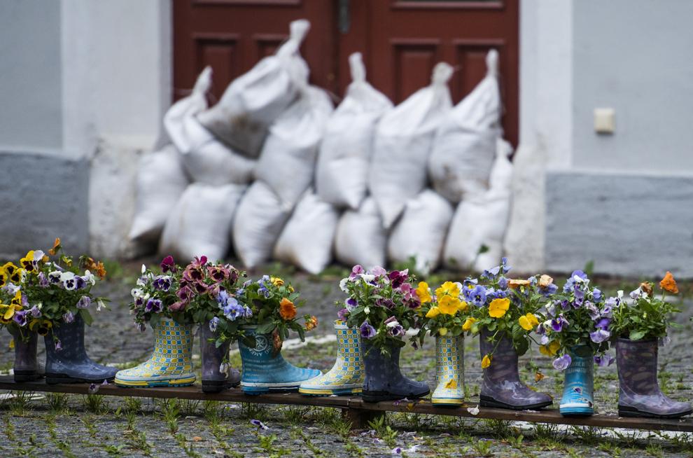 Cizme de cauciuc umplute cu flori sunt aşezate în faţa intrării unei case protejate cu saci umpluţi cu nisip, în Meissen, estul Germaniei, marţi, 4 iunie, 2013.
