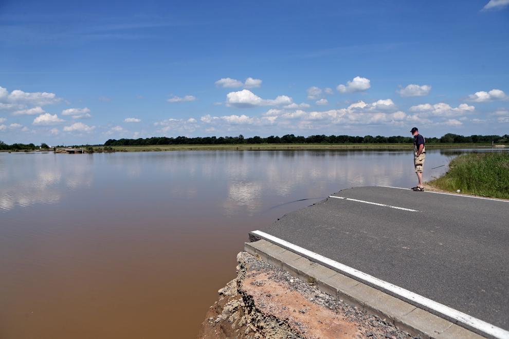 Un bărbat stă la marginea unui drum rupt de ape, lângă Loebnitz, sudul Germaniei, vineri, 7 iunie, 2013.