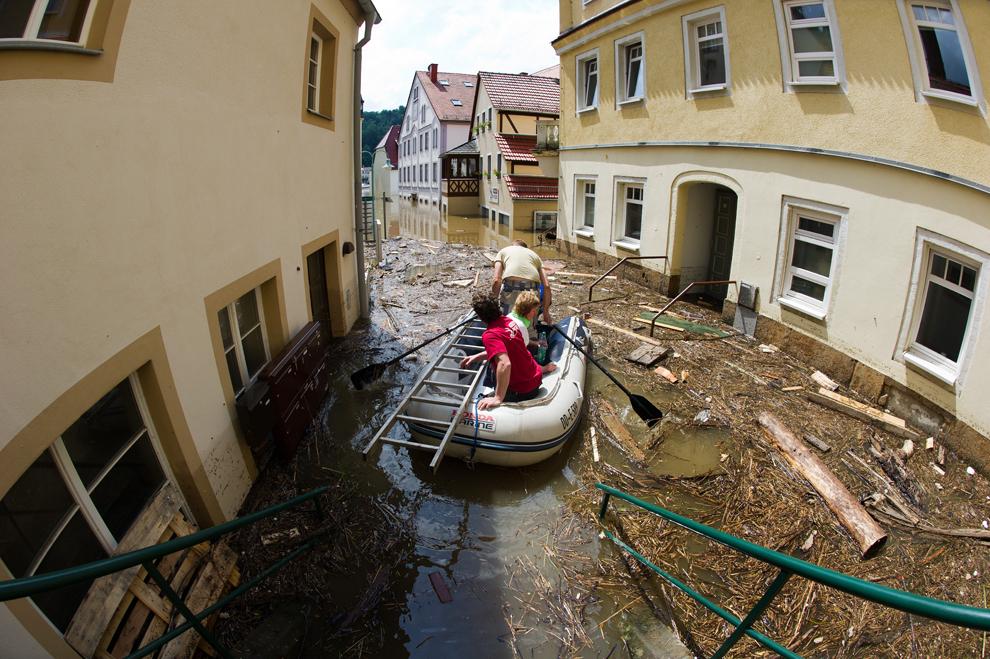 Folosind o ambarcaţiune de cauciuc, oameni traversează străzile inundate de râul Elba, în oraşul Stadt Wehlen, sudul Germaniei, vineri, 7 iunie, 2013.