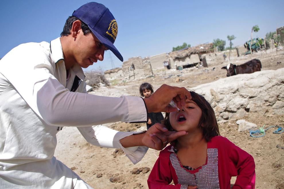 Un angajat al sistemul sanitar afgan (S)  vaccinează împotriva poliomielitei un copil, în tabăra de refugiaţi de la Laghman, duminica, 9 iunie 2103.