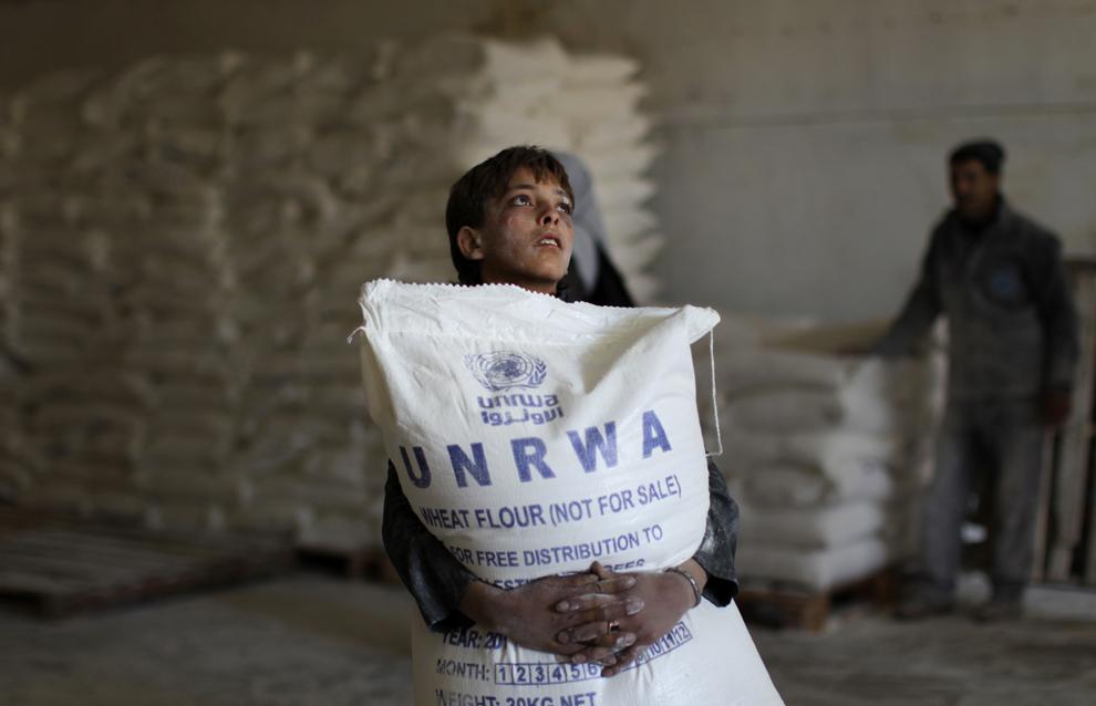 Un copil palestinian ţine un sac de făină în mână, la punctul de distribuire a ajutoarelor ONU din Fâşia Gaza, miercuri, 10 aprilie 2013.