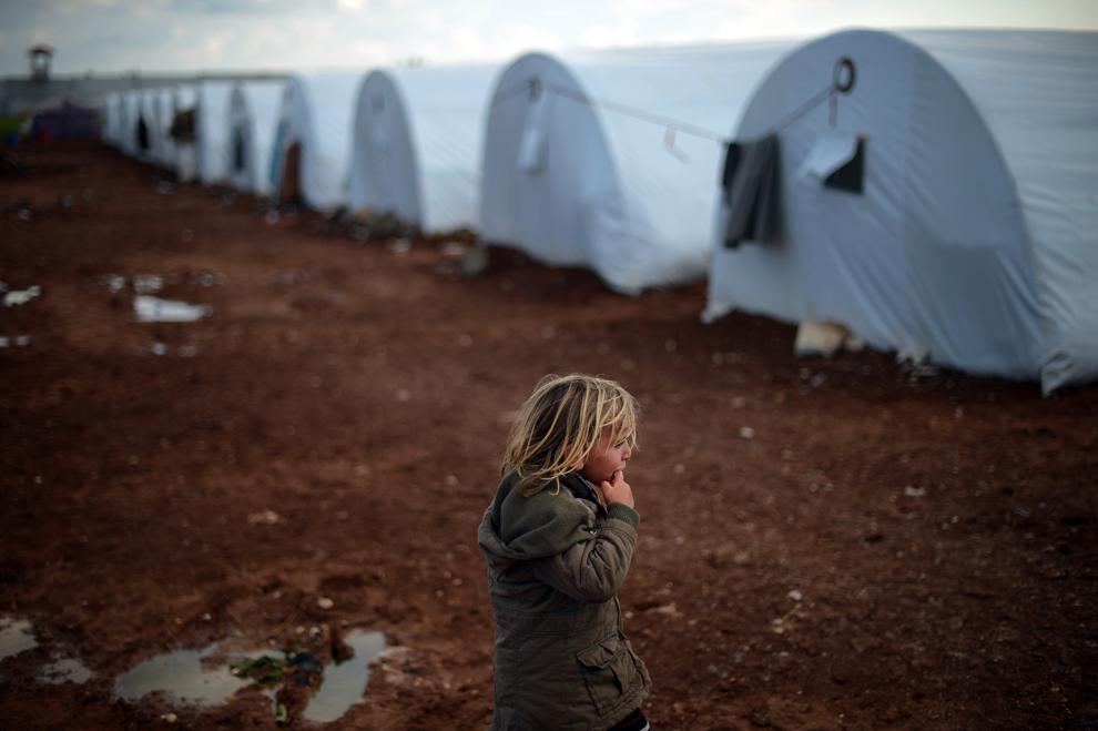 O fetiţă refugiată de origine siriană poate fi vazută lângă corturi, în tabăra de refugiaţi Maiber al-Salam de la graniţa cu Turcia, în provincia Alepp, miercuri, 17 aprilie 2013.