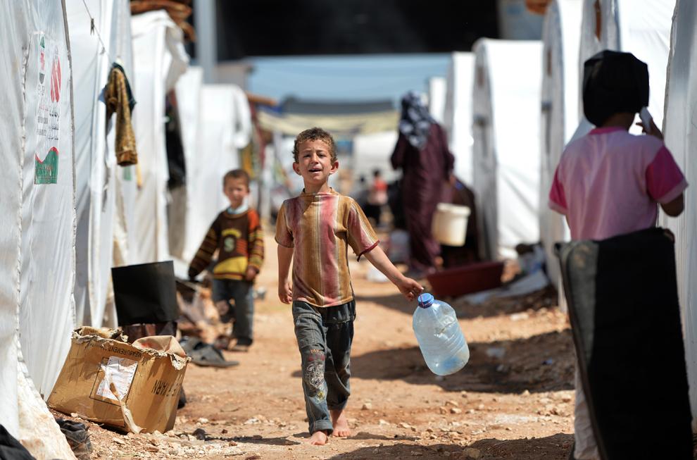 Familii de sirieni evacuaţi din locuinţe îşi petrec timpul în tabăra Maiber al-Salam de-a lungul graniţei turce, în provincia Alepp, duminică, 28 aprilie 2013.
