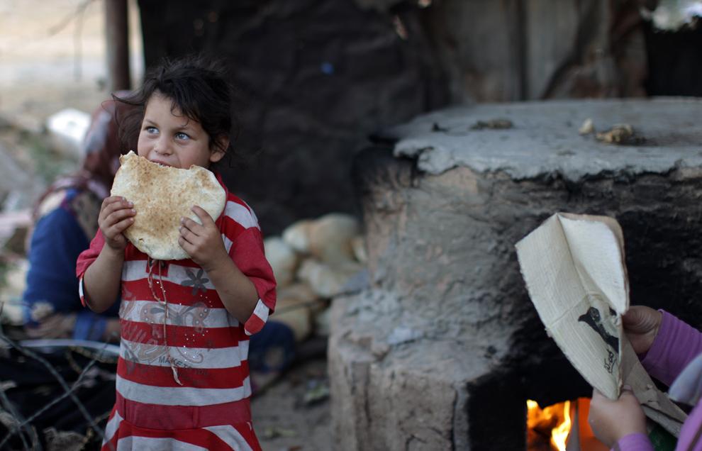 O fetiţă palestiniană refugiată mănâncă pâine într-un cartier sărac al oraşului Beith Lahia, în nordul Fâşiei Gaza, duminică, 28 aprilie 2013.