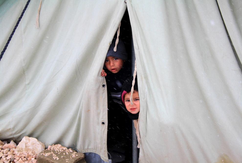 Copii sirieni refugiaţi privesc dintr-un cort furnizat de UNHCR în Al-Marj, în estul văii libaneze Bekaa, miercuri, 9 ianuarie 2013.