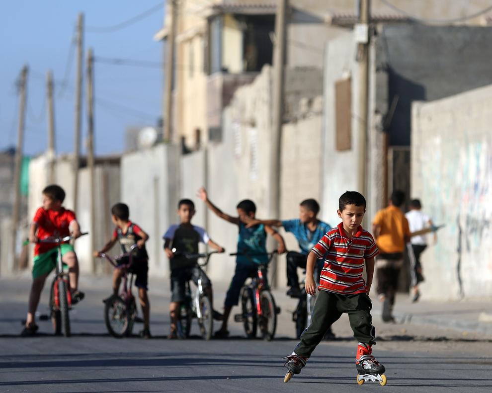 Un copil palestinian merge pe role în tabăra de refugiaţi Shati din oraşul Gaza, vineri, 29 martie 2013.