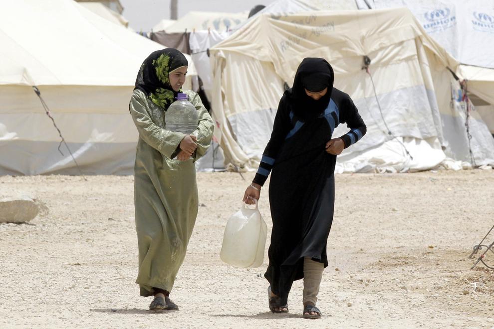 Refugiaţi sirieni cară apă în vase de plastic în timp ce traversează tabăra iordaniană din Zatari, casă pentru 160,000 de refugiaţi sirieni, sâmbătă, 18 mai 2013.