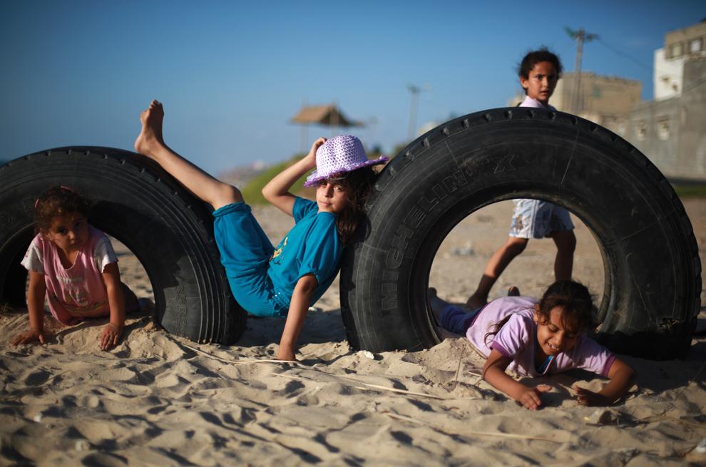 Copii palestinieni îşi petrec timpul pe o plajă de lângă tabăra de refugiaţi Deir al-Balah, pe ţărmul Mediteranei, în zona de centru a Fâşiei Gaza, vineri,  14 iunie 2013.