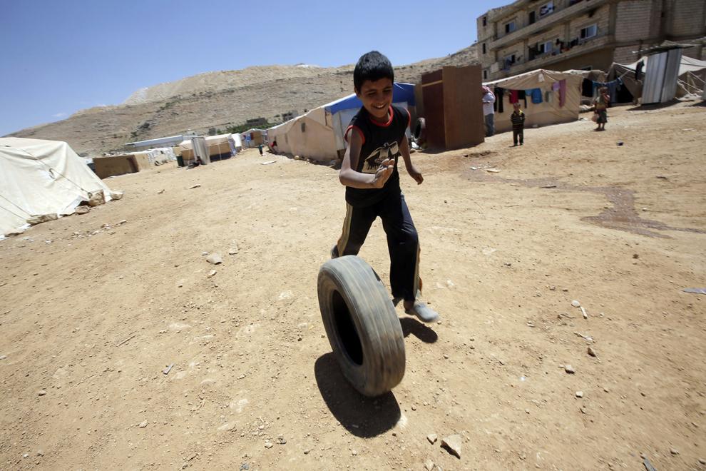 Un băiat sirian, refugiat alături de familia lui din calea violenţelor din Qusayr, se joacă cu un cauciuc în tabăra de refugiaţi Arsal, vineri,  14 iunie 2013.