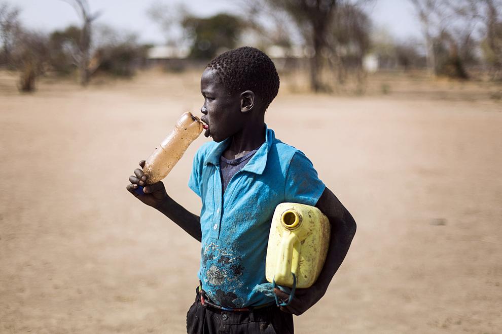 Un copil din Sudanul de Sud cară recipiente în care va aduce apă, în tabăra de refugiaţi JanJang, sâmbătă, 2 februarie 2013.