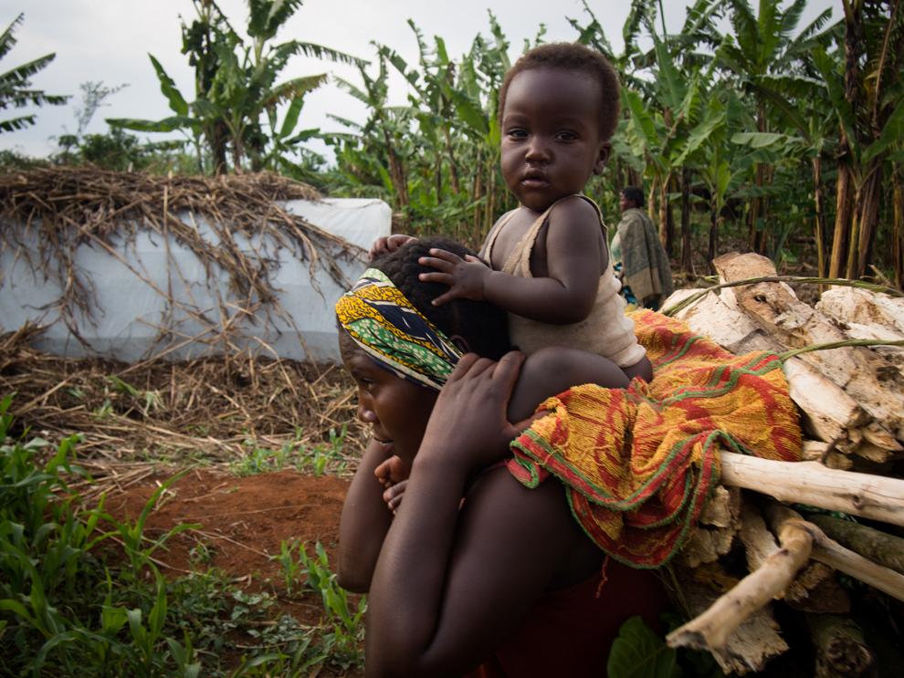 O femeie cară lemne de foc şi copilul său, în tabăra de refugiaţi Rwamwanja din Uganda, acolo unde sunt gazduiţi peste 35.000 de refugiaţi din R.D. Congo, marţi, 5 martie 2013.