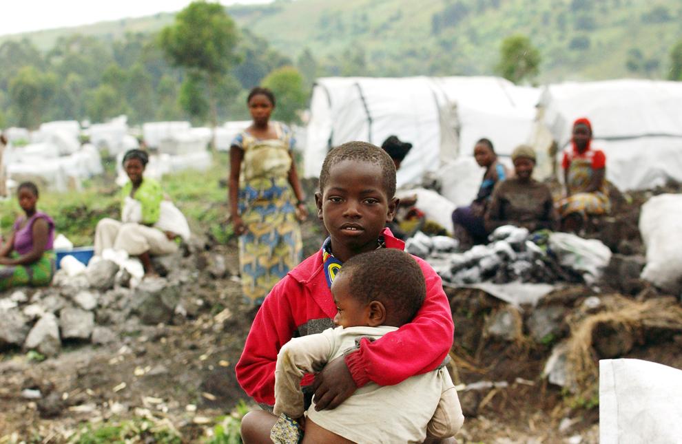 Un copil ţine în braţe un altul, printre adăposturile improvizate din tabăra de refugiaţi din Muganga, 15km de Goma, Congo,  sâmbătă, 25 mai 2013.