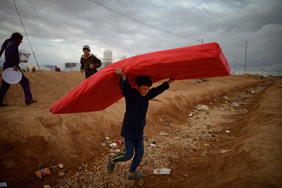 Un copil cară o saltea în timp ce refugiaţi sirieni îşi petrec ziua în tabăra de la Za'atari din Mafrq, Iordania, marţi, 29 ianuarie 2013.
