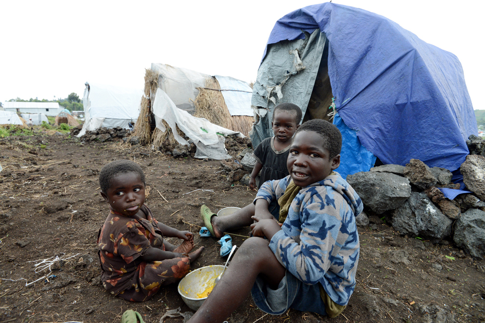 Copii mănâncă lângă un adăpost improvizat din tabăra de persoane evacuate din Muganga, 15km de Goma, Congo, sâmbătă, 25 mai 2013.