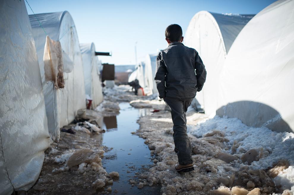 Un băiat merge pe o alee acoperită cu zăpadă, în tabăra de refugiaţi sirieni de la Azaaz, lângă graniţa cu Turcia, joi, 10 ianurie 2013.