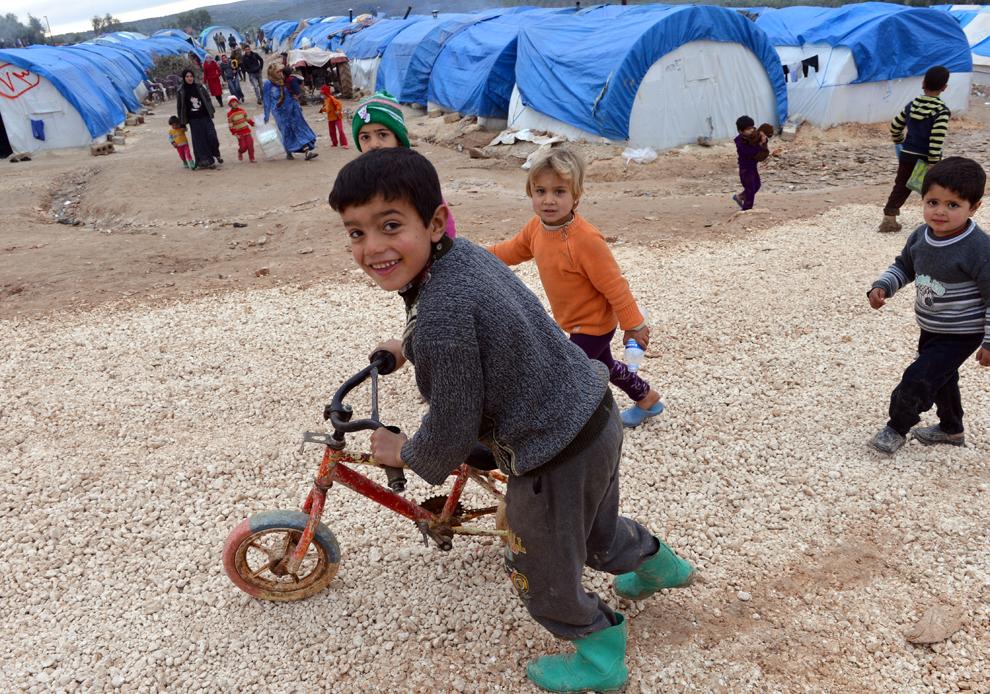 Copii sirieni refugiaţi se joacă în afara corturilor, în tabăra de refugiaţi din Qah, în zona graniţei cu Turcia, în provincia Idlib, joi, 7 februarie 2013.