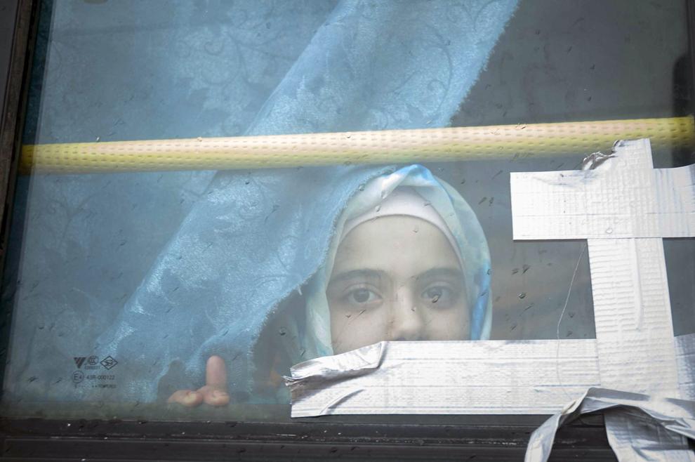 O fată de originie siriană priveşte pe geamul unui autobuz spre tabăra de refugiaţi Bab al-Salam de pe graniţa turco-siriană, joi, 28 februarie 2013.