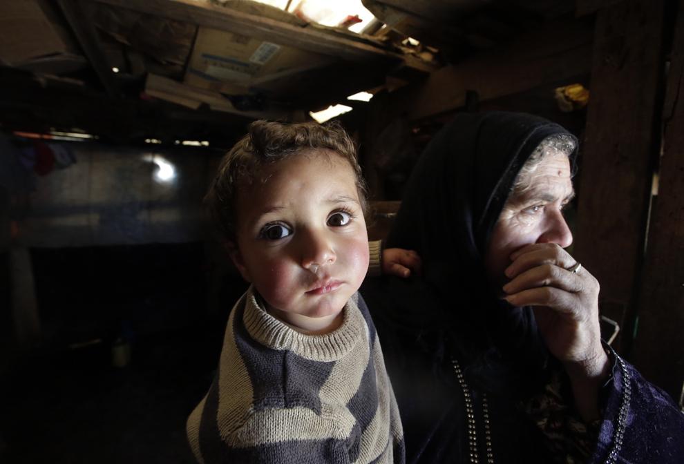 O bătrână de origine siriană îşi cară nepotul de doi ani, Mohammed, care, conform spuselor ei, s-a născut în ziua în care a izbucnit revoluţia siriană, în tabăra de refugiaţi  din satul Saadnayel, miercuri, 6 martie 2013.