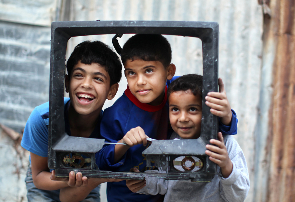 Trei copii palestinieni pozează ţinând în mâini carcasa unui televizor defect, în tabăra de refugiaţi al-Shati, în oraşul Gaza, miercuri, 13 martie 2013.