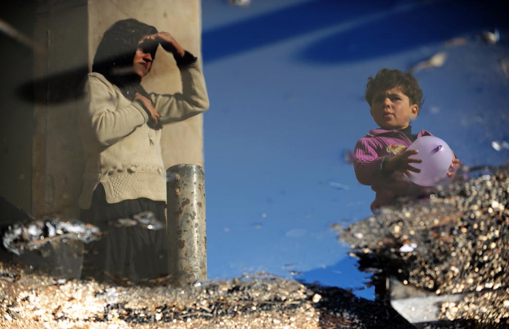 Imaginea unei femei de origine siriană şi a unui copil se reflectă într-o baltă cu apă în tabăra de refugiaţi Bab al-Hawa de la graniţa cu Turcia, în provincia siriană Idlib, luni, 18 martie 2013.