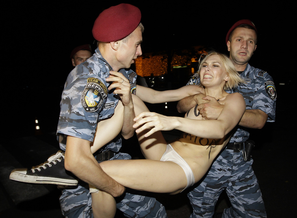 O imagine distribuită de serviciul de presă al Femen arată o activistă Femen în timp ce este arestată în Kiev, luni, 17 iunie 2013.