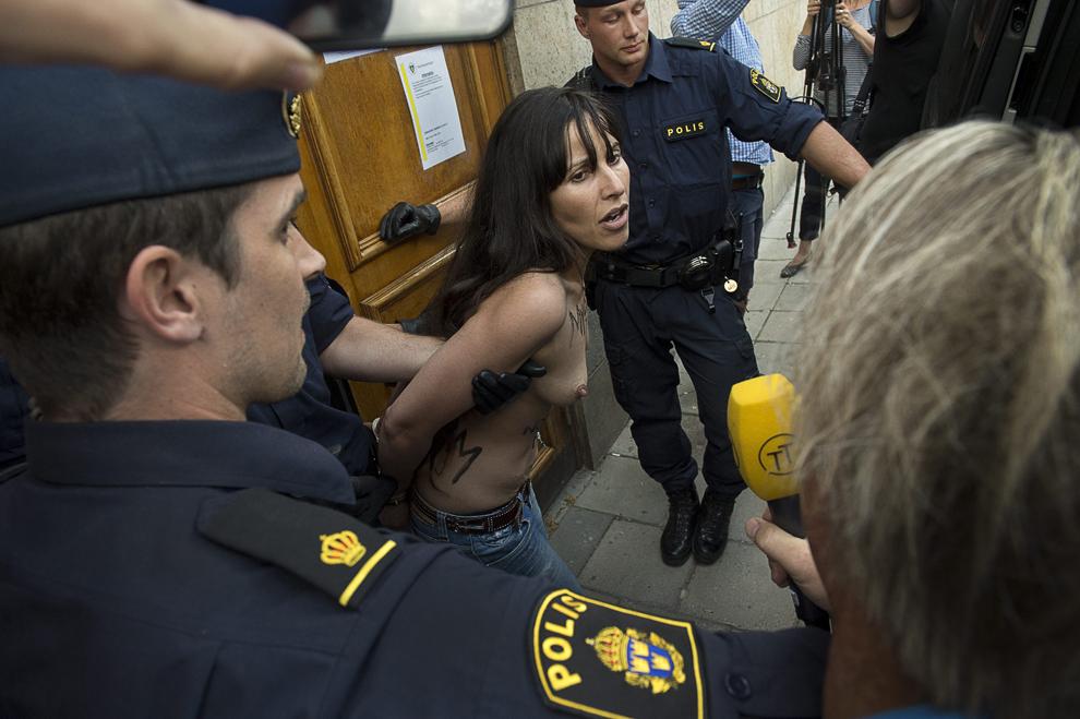 Poliţişti reţin o activistă topless din grupul feminist Femen după ce aceasta a protestat pentru drepturile femeilor şi pentru a sprijini opoziţia din Egipt, într-o moschee din Stockholm, sâmbătă, 29 iunie 2013.