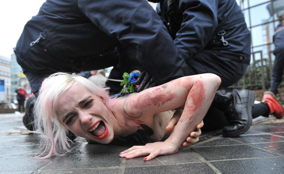 O activistă a mişcării feministe Femen din Ucraina este luat de poliţie, în timpul unui protest organizat în faţa clădirii Consiliului UE, la Bruxelles, vineri, 21 decembrie 2012.