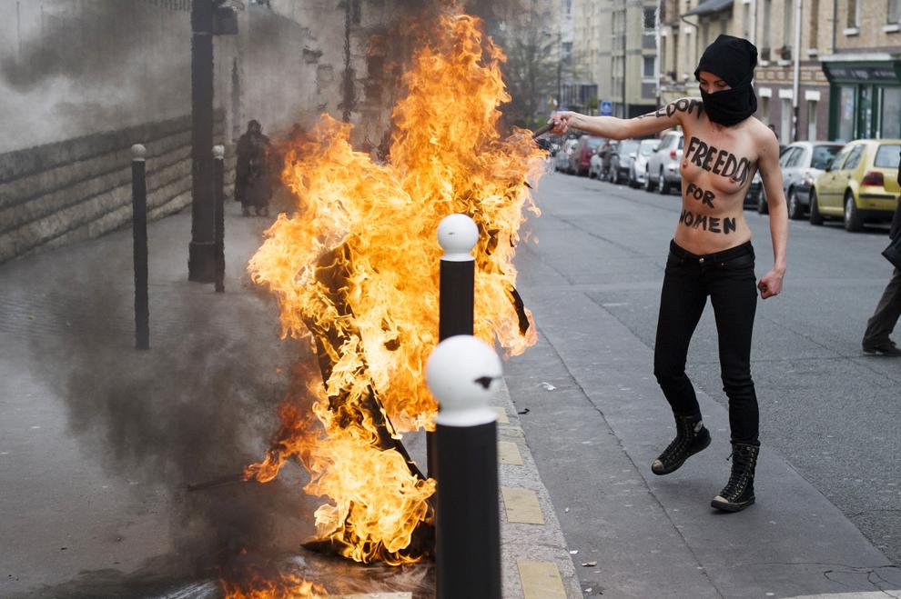 O activistă, membră a grupării feministe Femen, protestează arzând un steag al mişcării Salafist, în faţa Marii Moschei din Paris, miercuri, 3 aprilie 2013.