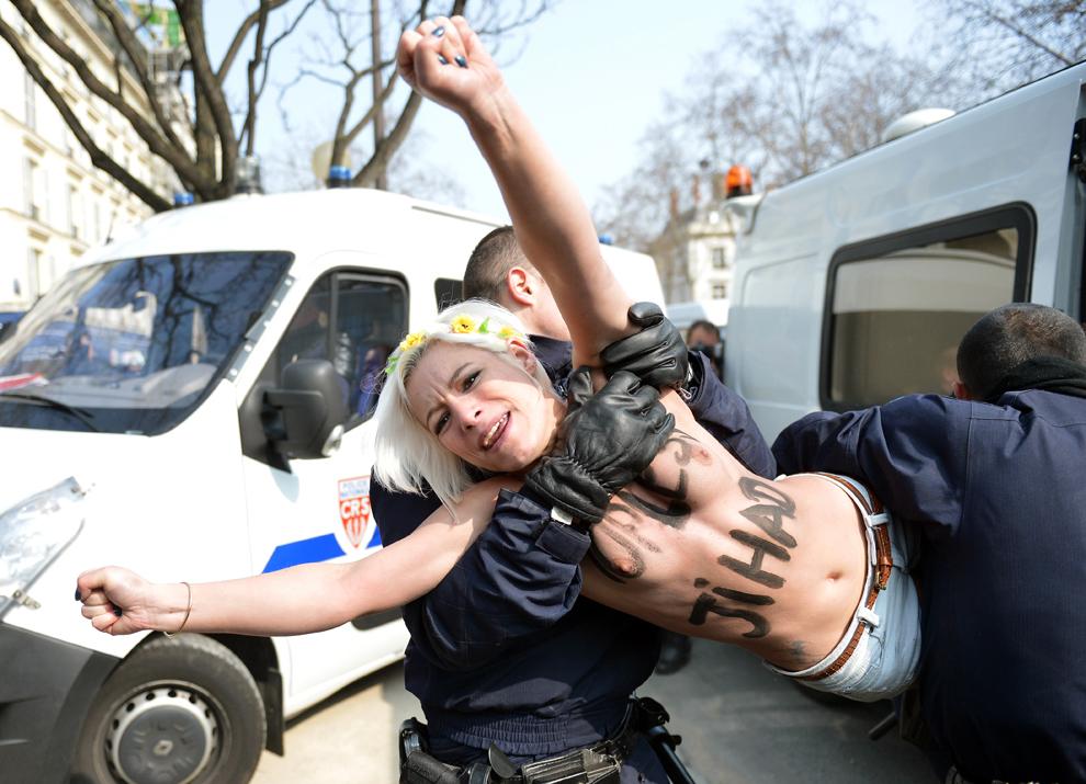 O activistă a mişcării Femen este îndepărtată de către poliţişti, în timpul unui protest topless lângă ambasada Tunisiei, la Paris, joi, 4 aprilie 2013.