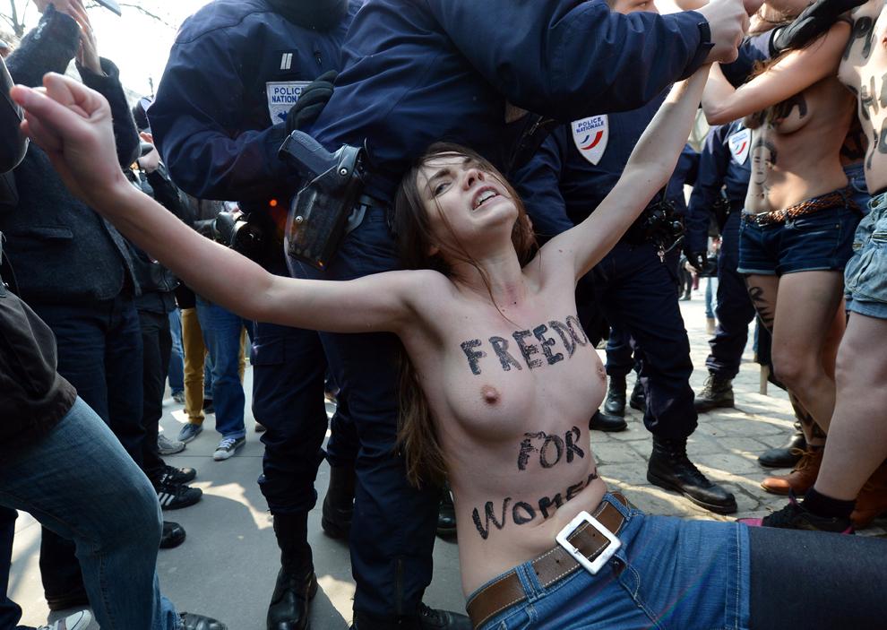 O activistă a mişcării Femen este îndepărtată de către poliţişti în timpul unui protest topless lângă ambasada Tunisiei, la Paris, joi, 4 aprilie 2013.