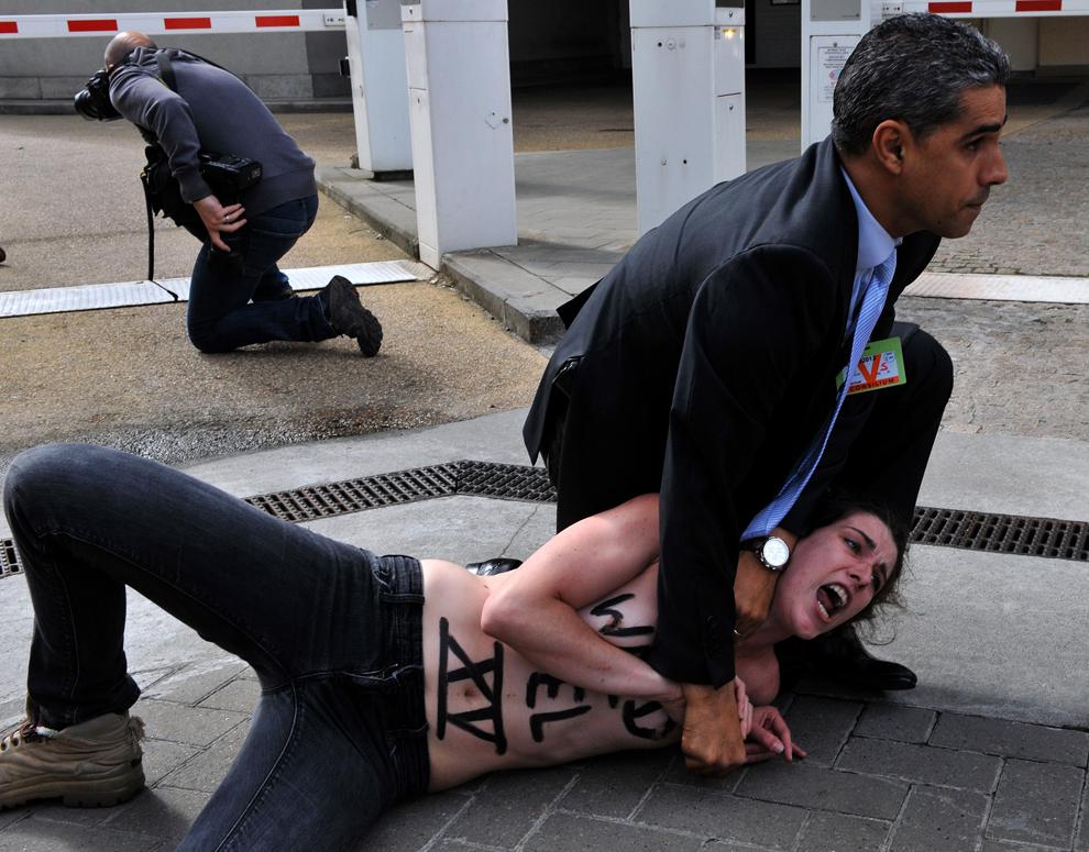 Un agent de pază imobilizează o activistă Femen după ce aceasta a încercat să oprească coloana oficială a primului ministru tunisian, marţi, 25 iunie 2013.
