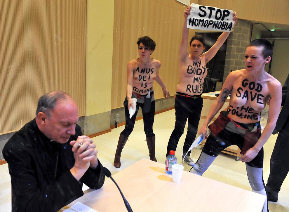 Arhiepiscopul Andre-Joseph Leonard este stropit cu apă de activiste Femen ce protestează împotriva homofobiei, în Bruxelles, marţi, 23 aprilie 2013.
